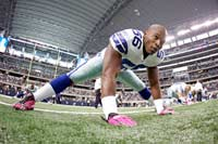 Dallas Cowboys linebacker Bradie James (56) wears pink gloves and cleats to honor NFL Breast Cancer Awareness Month.