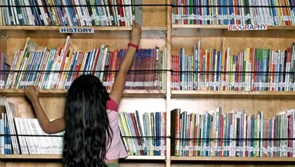 Young girl reaches for a book to read from an upper library shelf - Experience Corps places tutors in schools.