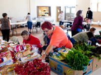 Robin Martin, 62, center, receives groceries from a mobile food bank and volunteers to help distribute them.