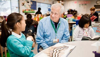 AARP Experience Corps tutor Fred Brundage assists third graders Amy Chang, left, and Thiri Than with their reading skills.