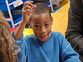 Child raising hand, AARP Experience Corps FAQs
