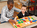 A woman and child play alphabet game, AARP Experience Corps History