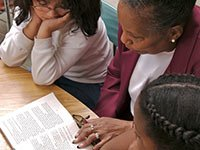 A woman reading to two girls, AARP Experience Corps Contact