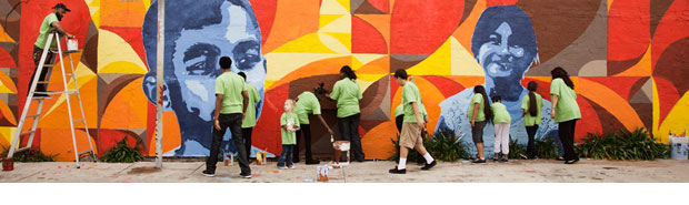 Volunteers with children painting a mural