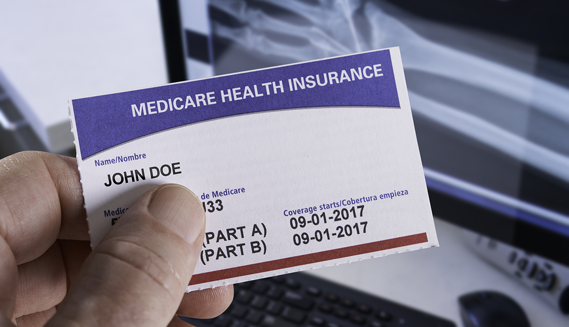 man's hand holding Medicare card in front of an x-ray