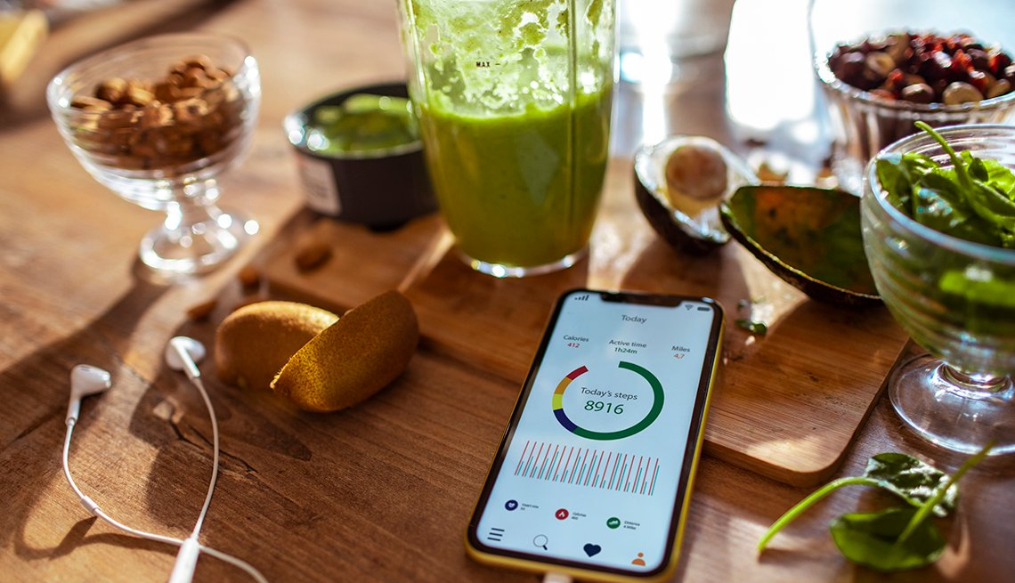 A phone with a step-tracking health app, a juice cleanse drink and healthy food in the background