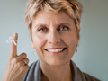 A smiling woman with a string on her finger, forgetfulness quiz.