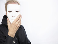 Mature man holding mask in front of face, Brain changes in older people may make them more prone to scams