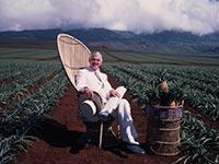 El empresario estadounidense David Murdock se relaja en una silla de mimbre en su plantación en Lanai, Hawaii.