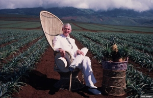American entrepreneur David Murdock relaxes on a wicker chair on his plantation in Lanai, Hawaii. A basket of pineapples sits on a table in front of him.  (Photo by Slim Aarons/Getty Images)