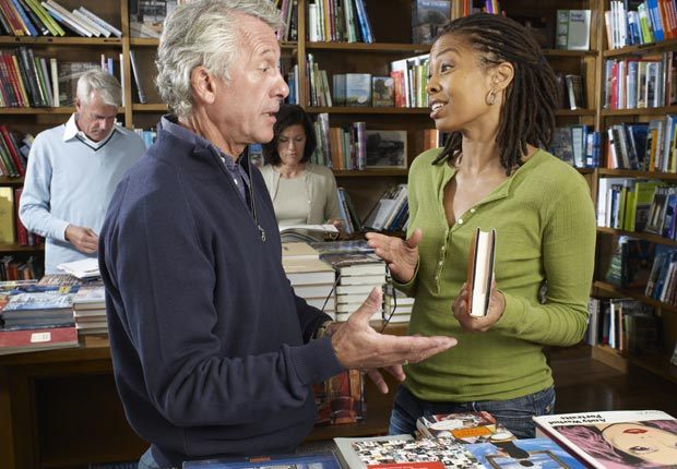Man talking to woman in bookstore, Risk reaching out (Yellow Dog Productions/Getty Images)