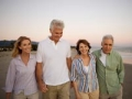 Group of mature friends walking on the beach, Brain Health Quiz on socializing. (UpperCut Images/Alamy)
