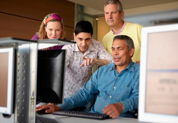 Adult students around a computer, Socialization and brain health, Learning (Image Source/Getty Images)