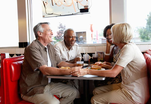 Two couples eating at retro diner, Socialization and brain health (Radius Images/Alamy)
