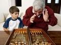 Niño y hombre jugando un juego de mesa - Juegos de la infancia para mejorar la salud cerebral