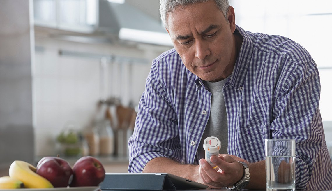 Hombre mirando un frasco de medicinas
