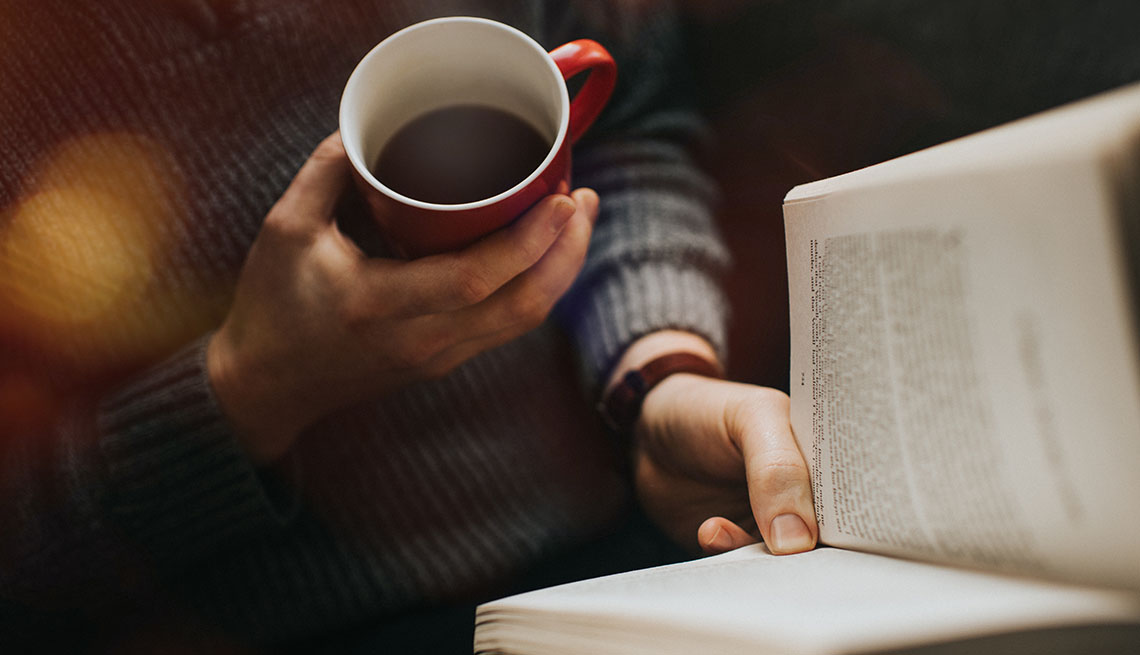 Male reading a book and drinking a hot drink from a red mug.