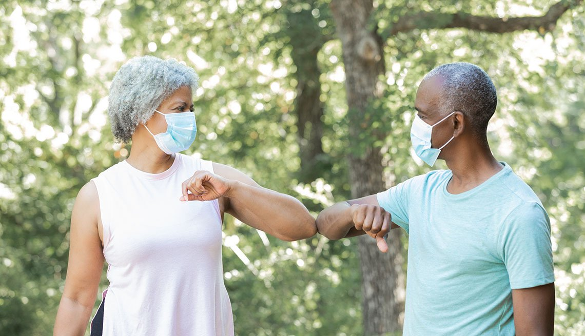 Senior man and woman wearing masks greet each other by touching elbows instead of shaking hands