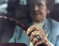 Mature woman's hand on steering wheel of car, close-up