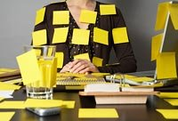 A woman with post-it notes all over her body and her desk.