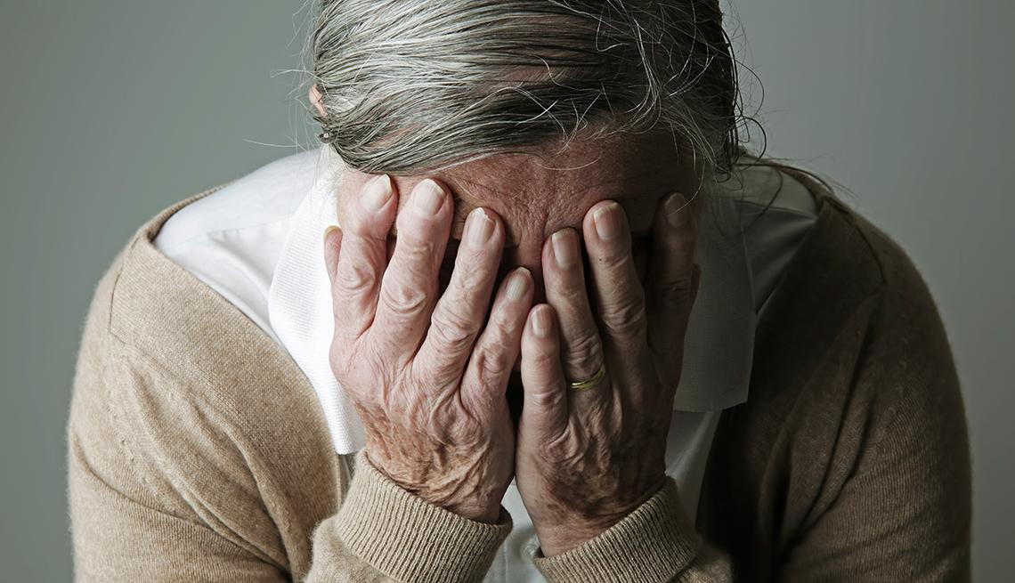 Persona mayor ocultando su cara en sus manos
