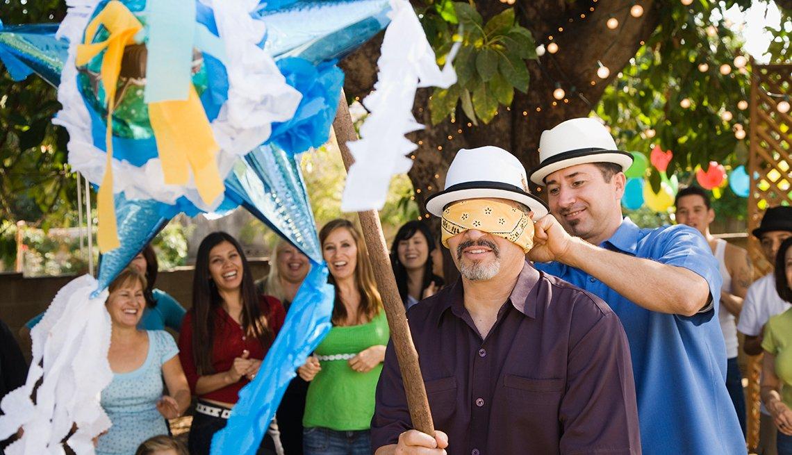Adultos rompiendo una piñata