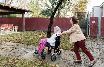 Mujer llevando a otra en sillón de ruedas