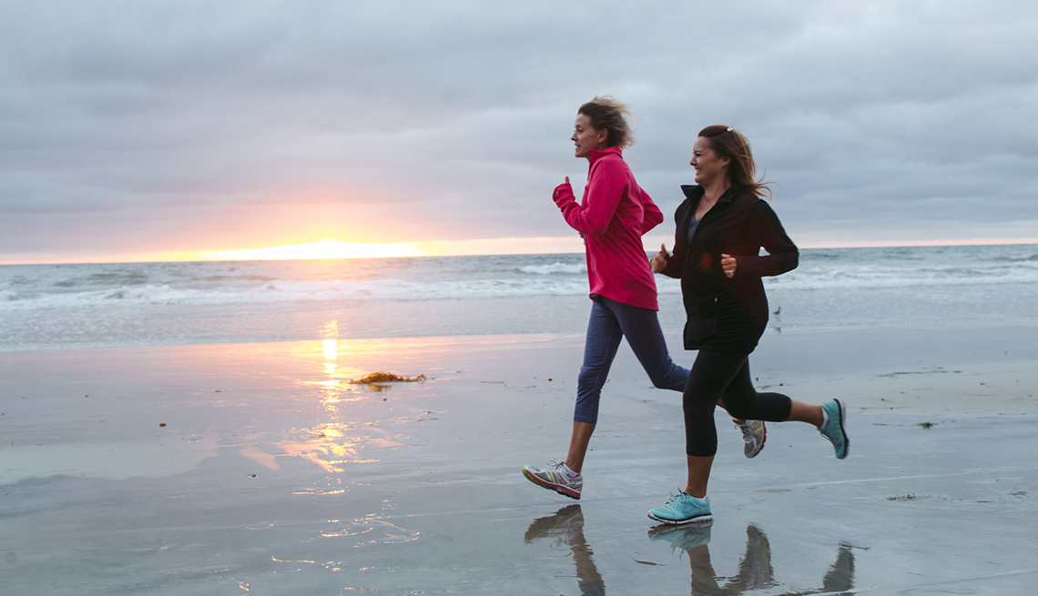 Dos mujeres corriendo por la orilla de la playa