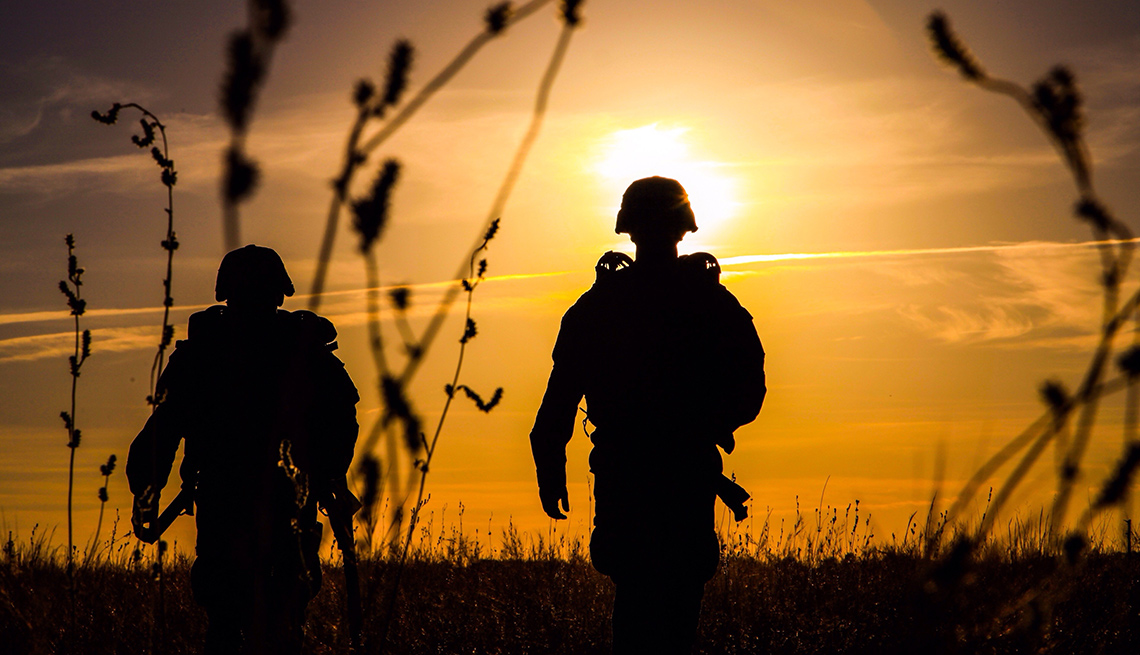 Two soldiers walking in a field at sunset