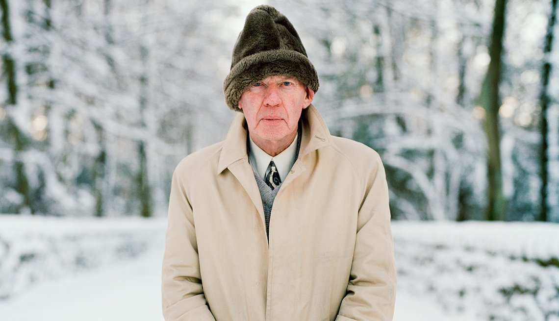 man standing outside in snowy landscape with hat and coat