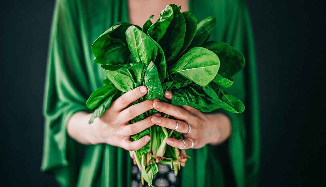 Young woman holding spinach leafs salad