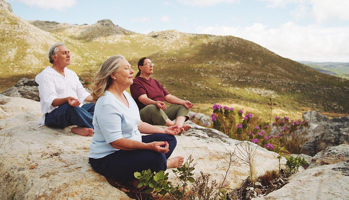 People meditating on hillside