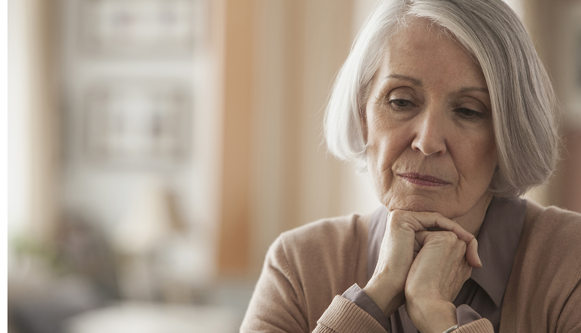 Older woman with chin in hands, looking sad