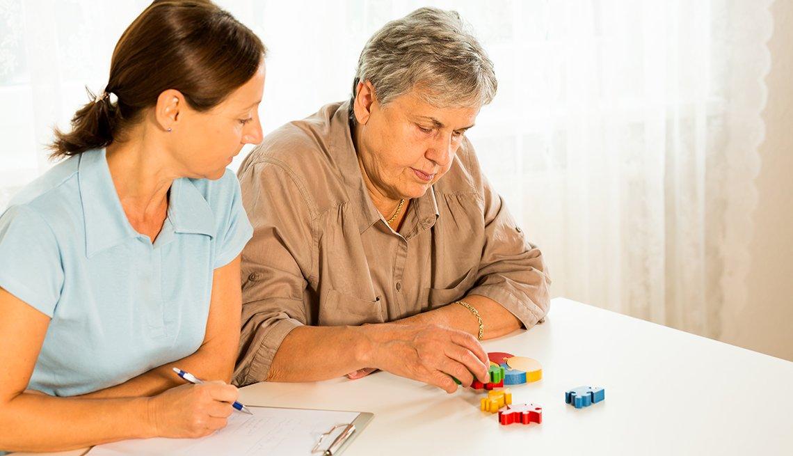 Mujer mayor armando un rompecabezas, mientras una persona la observa