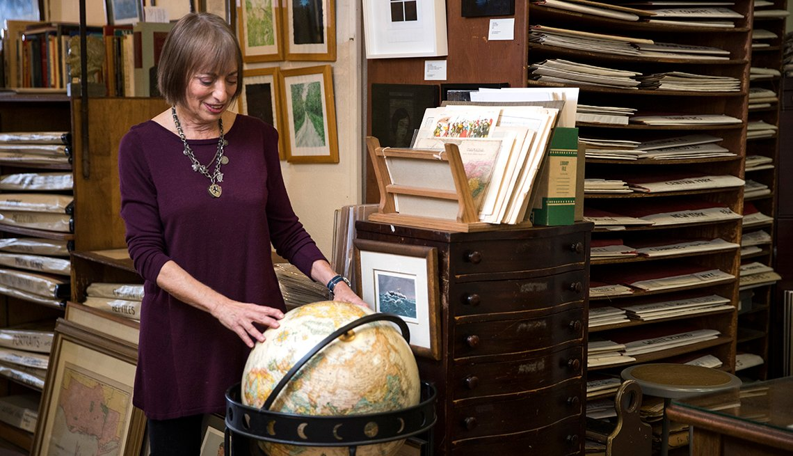 Novelist Catherine Hiller looking at a globe of the world
