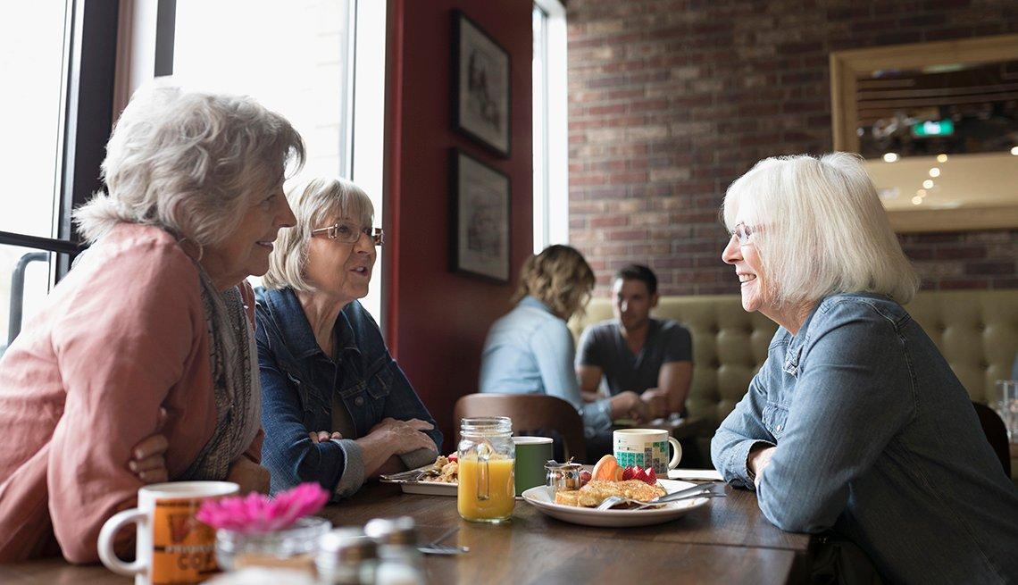 Tres mujeres comparten en un restaurante.