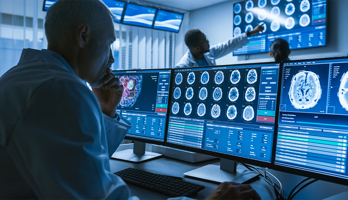 Over the Shoulder Shot of Senior Medical Scientist Working with CT Brain Scan Images on a computer