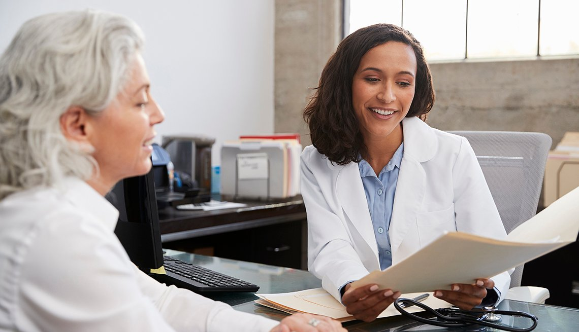 A doctor holding a folder discusses information with a female patient during a consultation