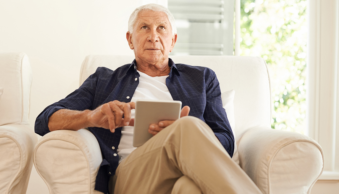 Hombre mayor sentado tratando de recordar algo mientras usa una tableta