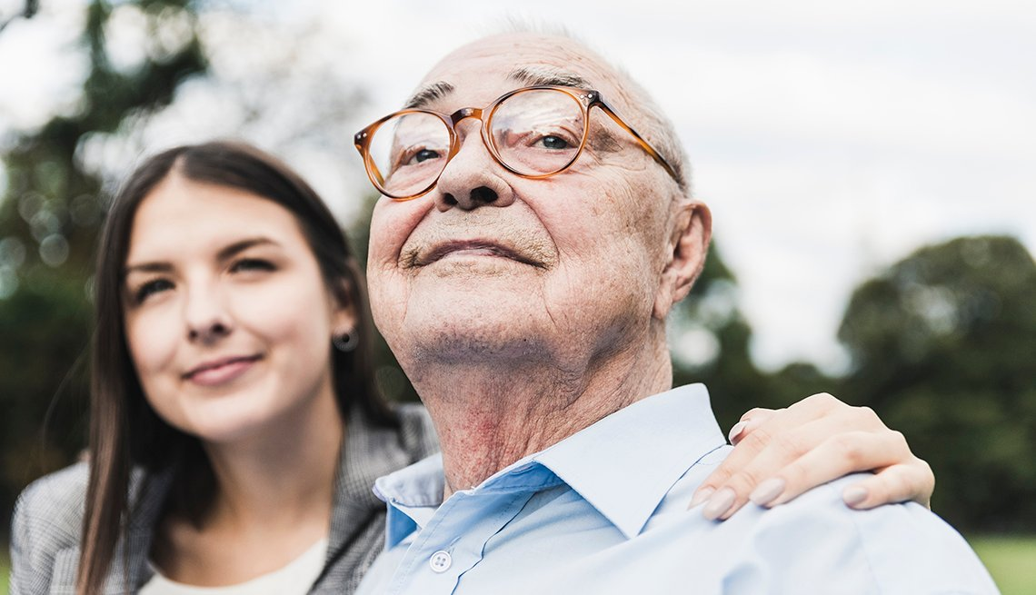Portrait of self-confident senior man with granddaughter in the background