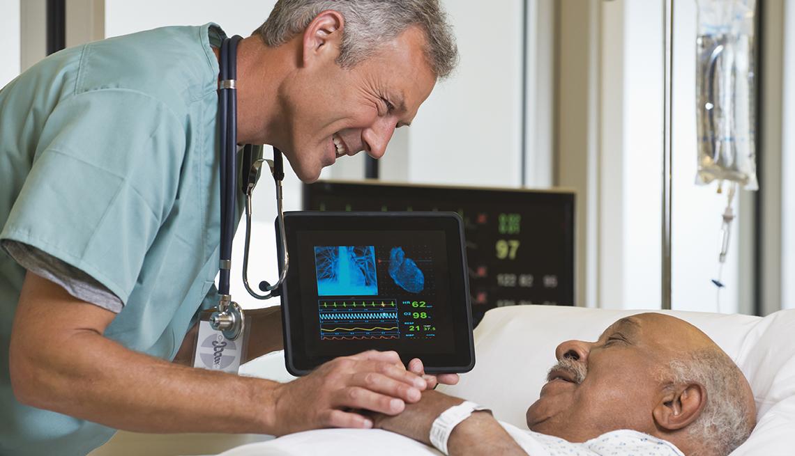 Un doctor se inclina para hablar con un paciente