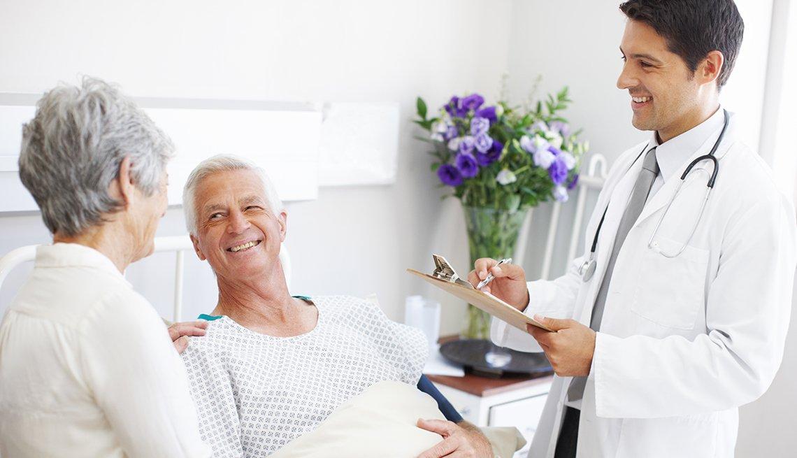 Un hombre hospitalizado recibe la visita de su esposa y también de su médico