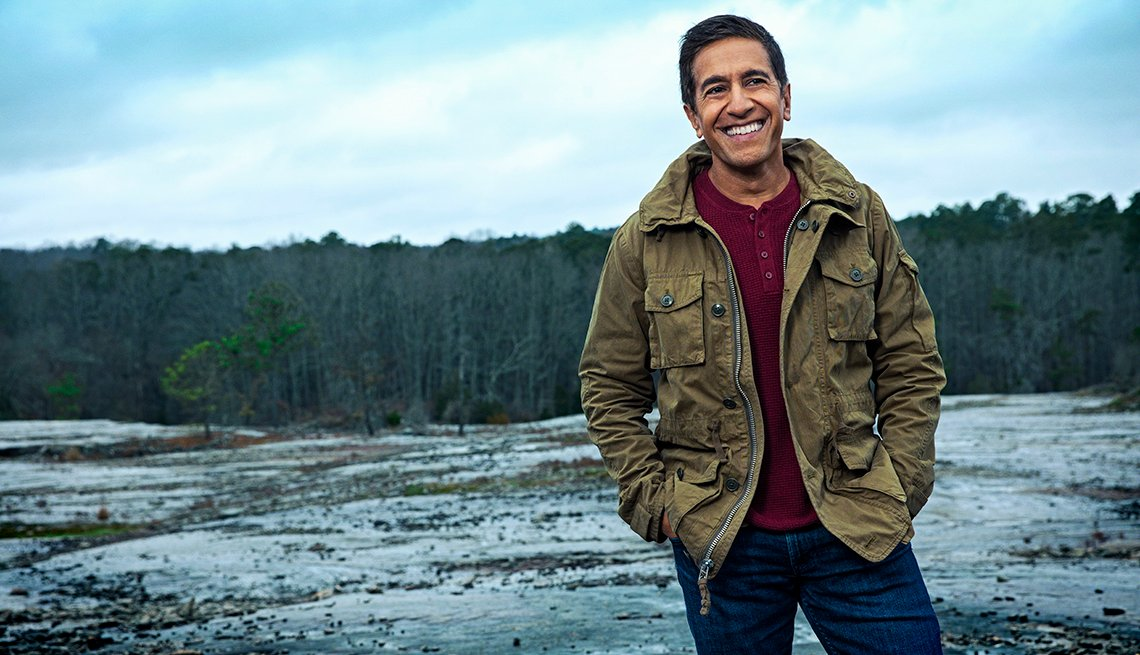 doctor sanjay gupta photographed outdoors smiling on a mountain peak