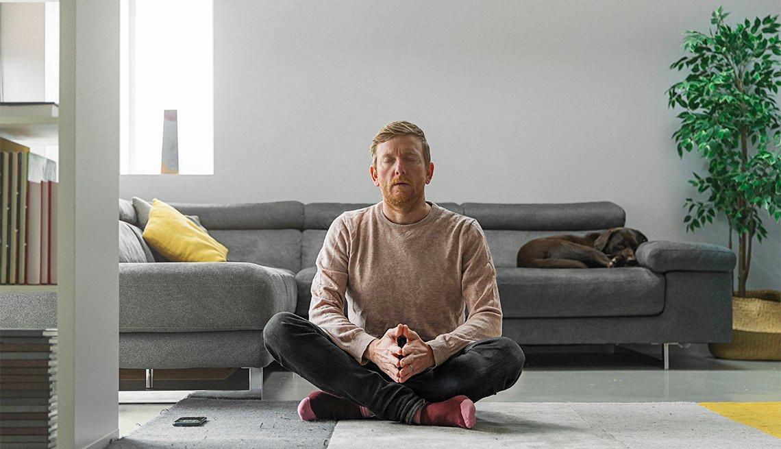 Un hombre medita sentado en el piso de su sala