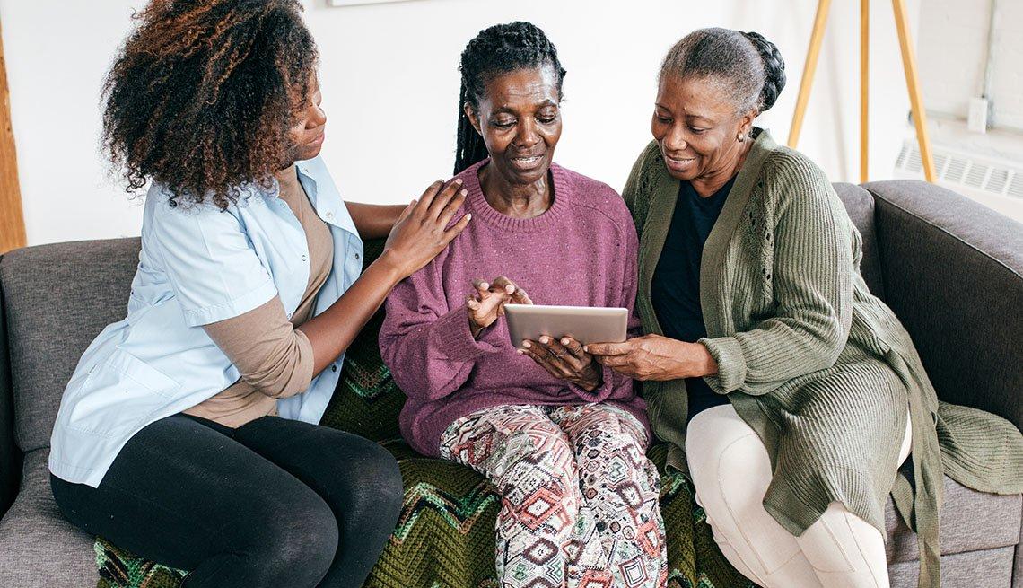 Tres mujeres sentadas en un sofá miran una tableta