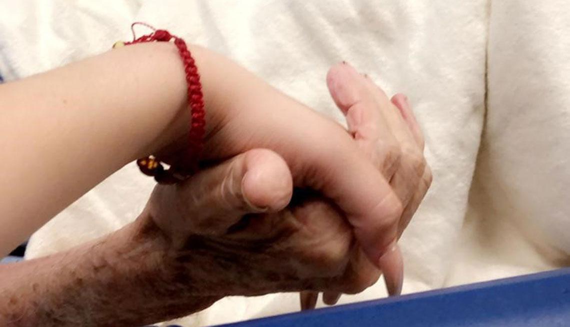 Dayana García sostiene las manos de su abuelo