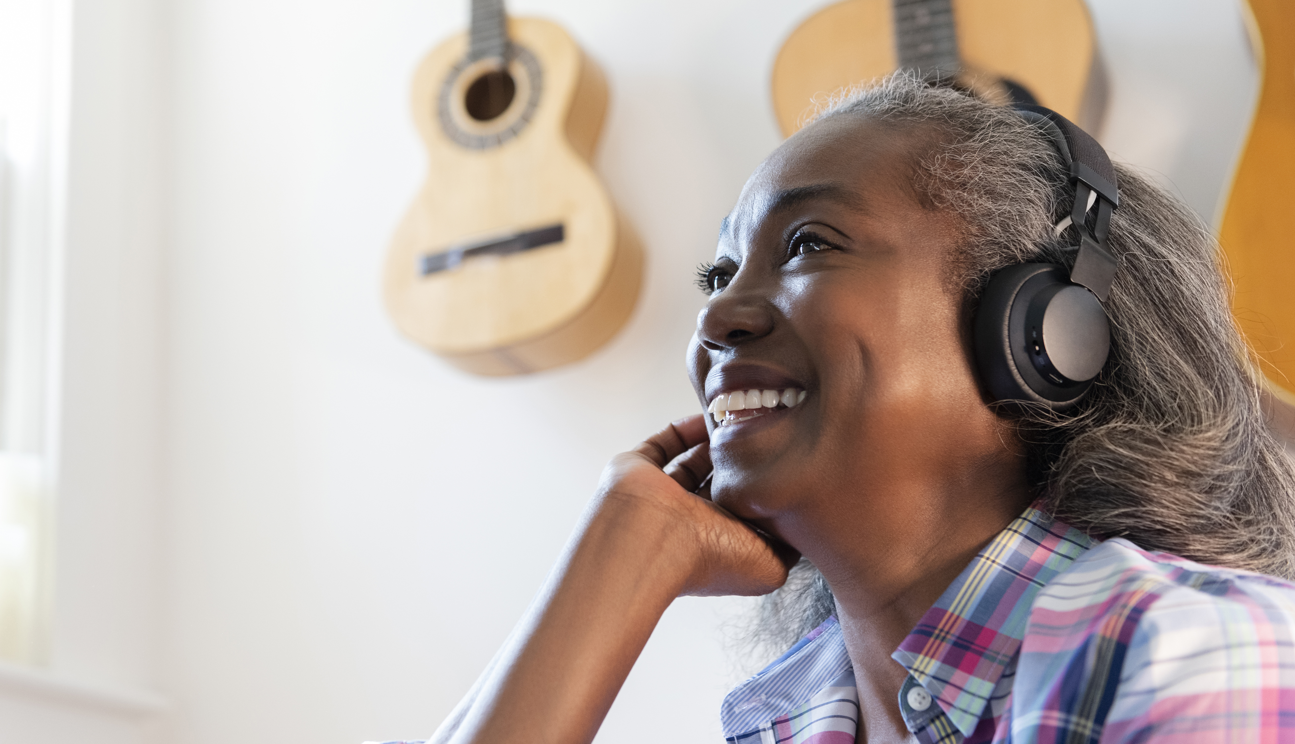 woman listening to music on headphones with guitars hung on the wall behind her