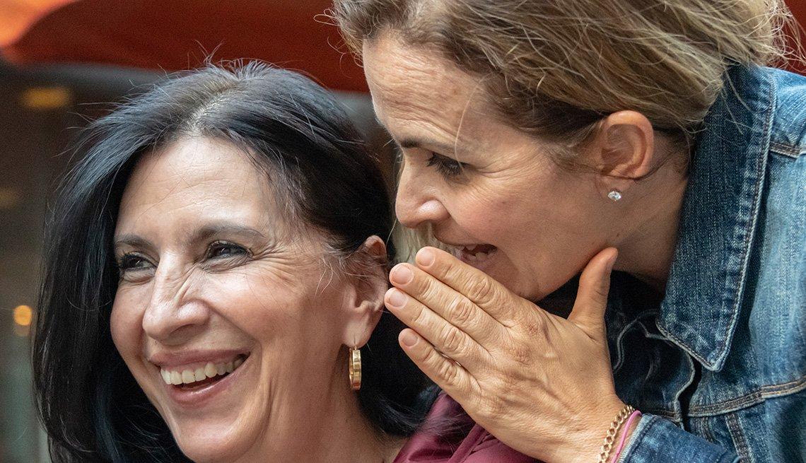 Una mujer susurra al oído de otra mujer