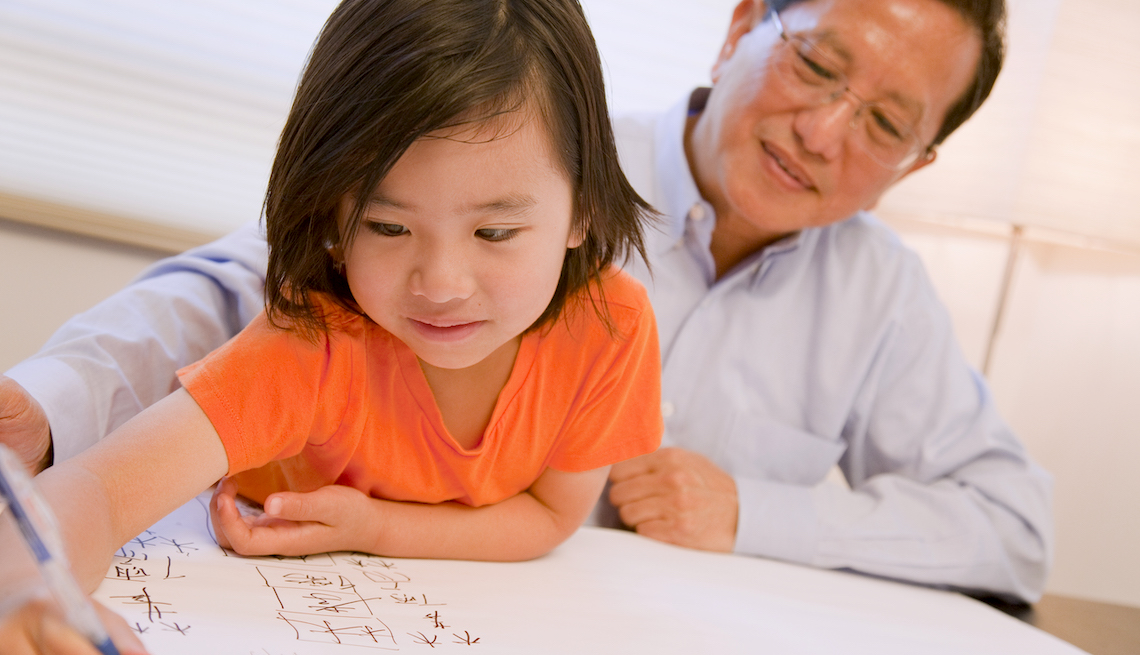 Chinese American grandfather watching his grandson writing