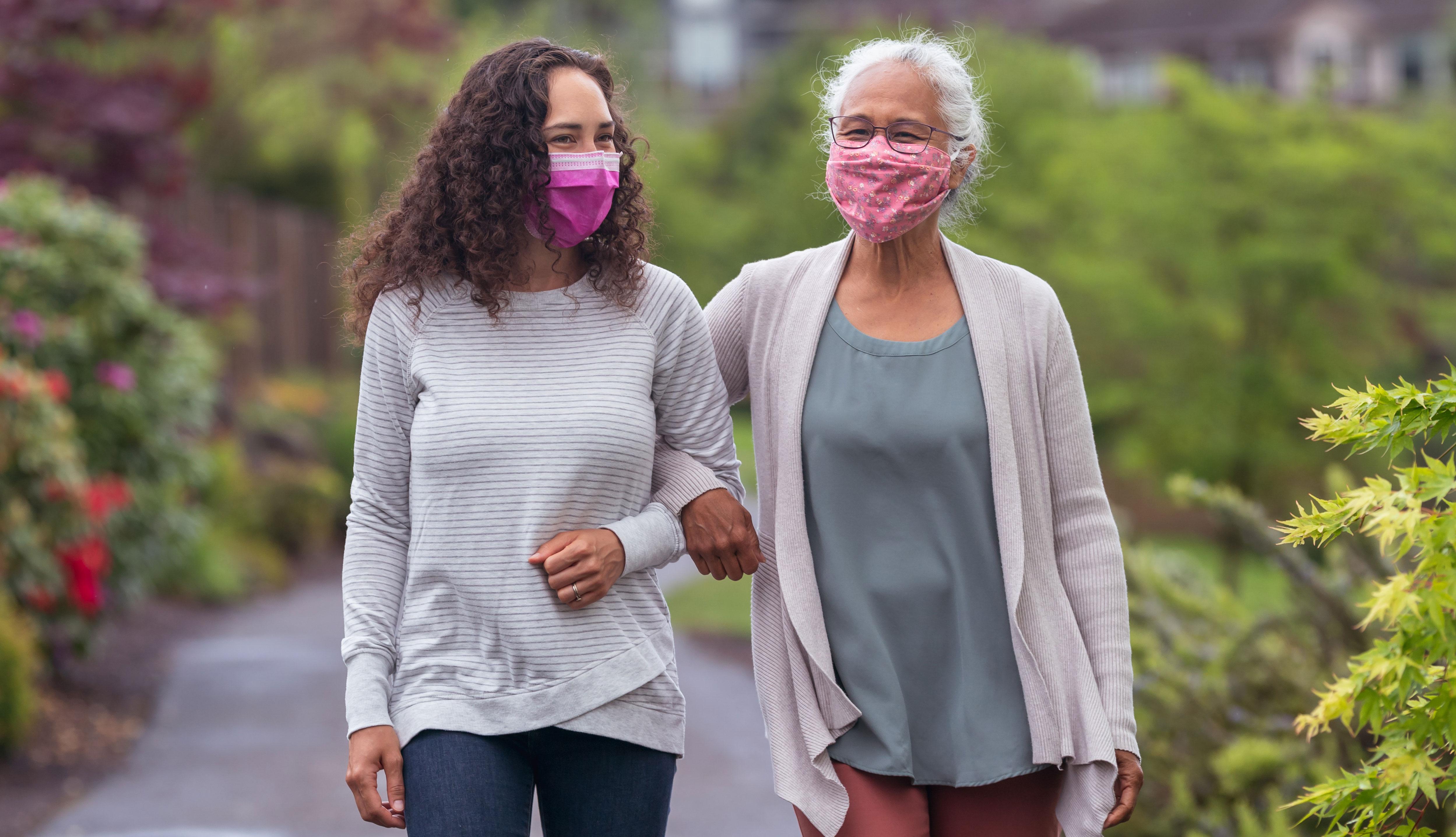 Dos mujeres, usando mascarillas, caminan al aire libre